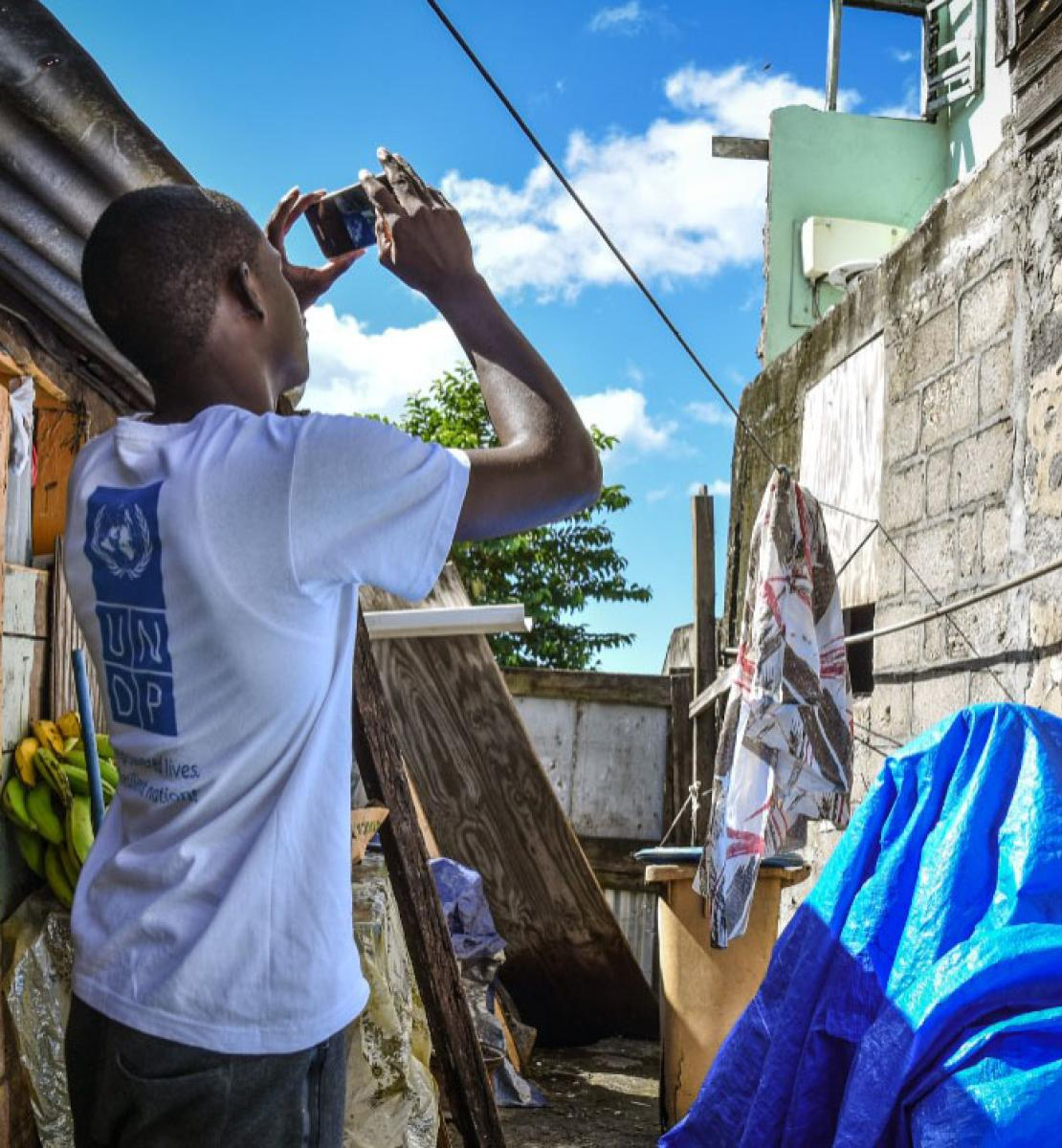UNDP assessor uses his mobile device to asses damage after a storm.