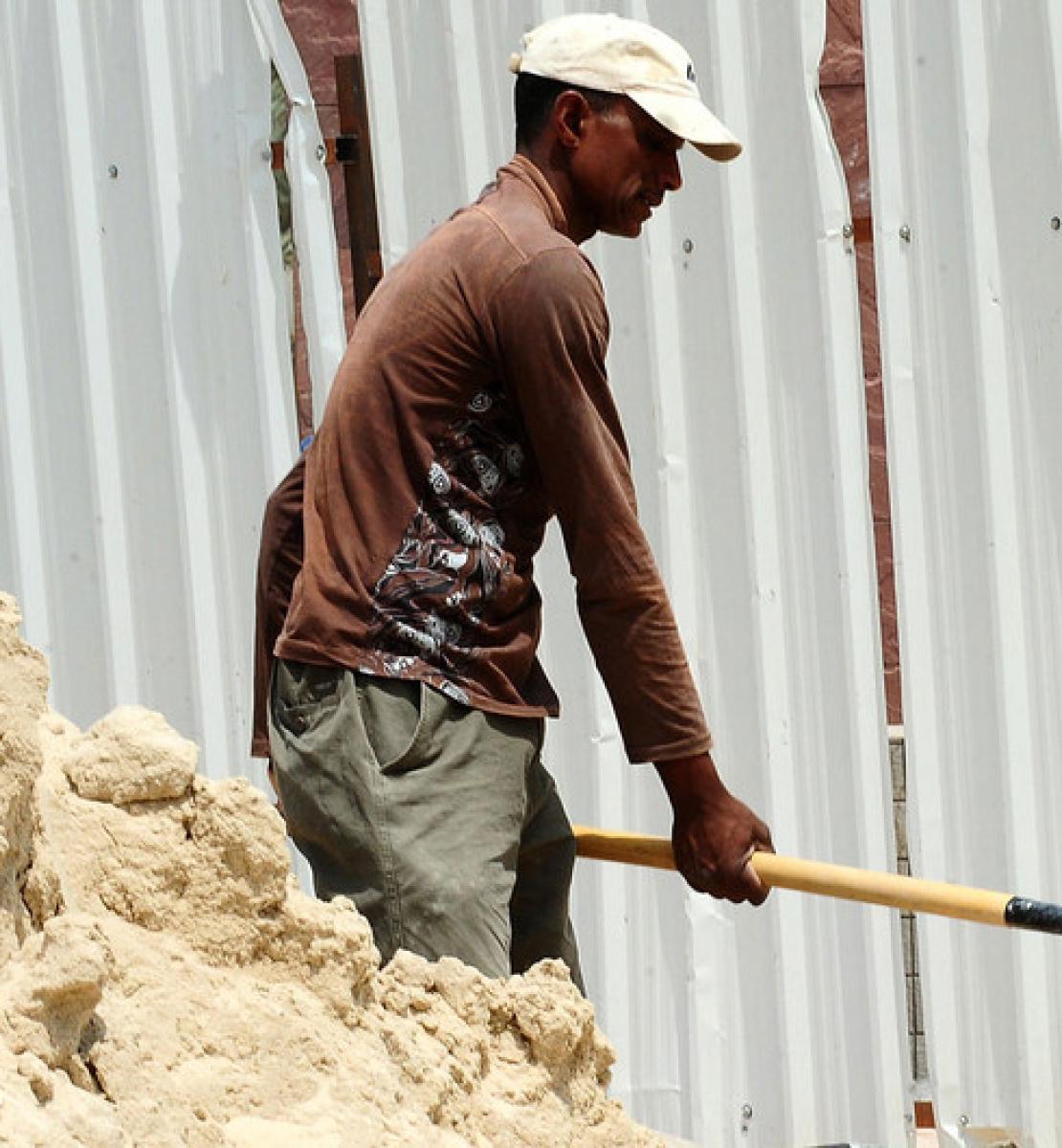 A labourer shoveling sand at a construction site.