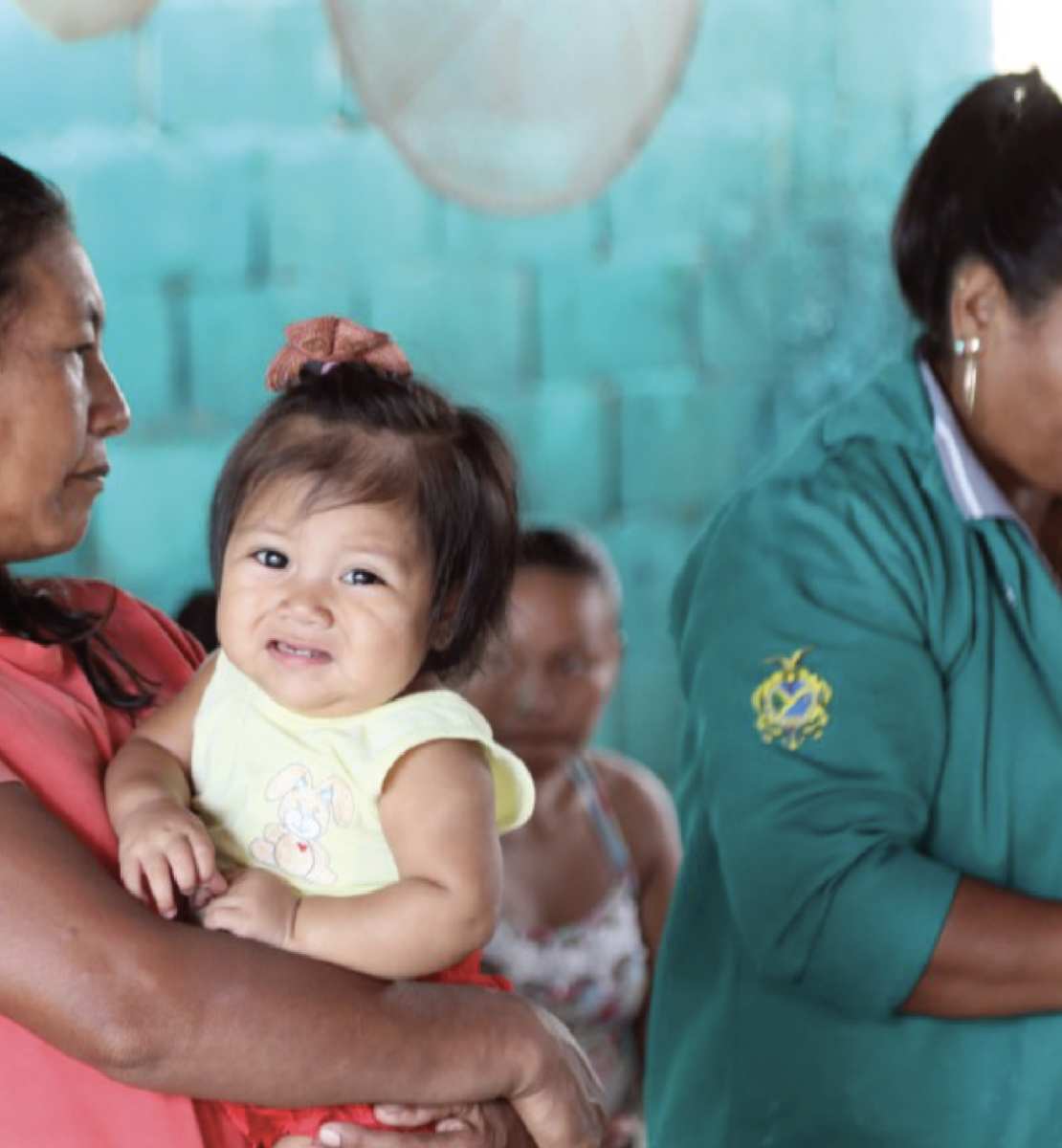 An indigenous woman holds a baby girl as she waits to be attended by a health worker.
