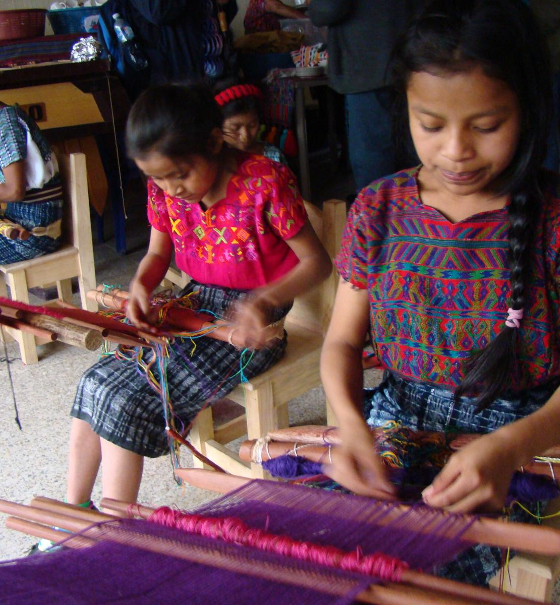 Photo showing three indigenous girls sitting on a chair and learning to weave using a traditional loom