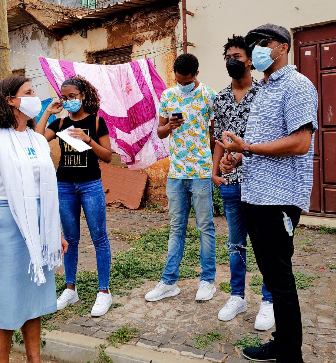 Resident Coordinator, Ana Patricia Graça, speaks outside a neighbourhood with young artists.