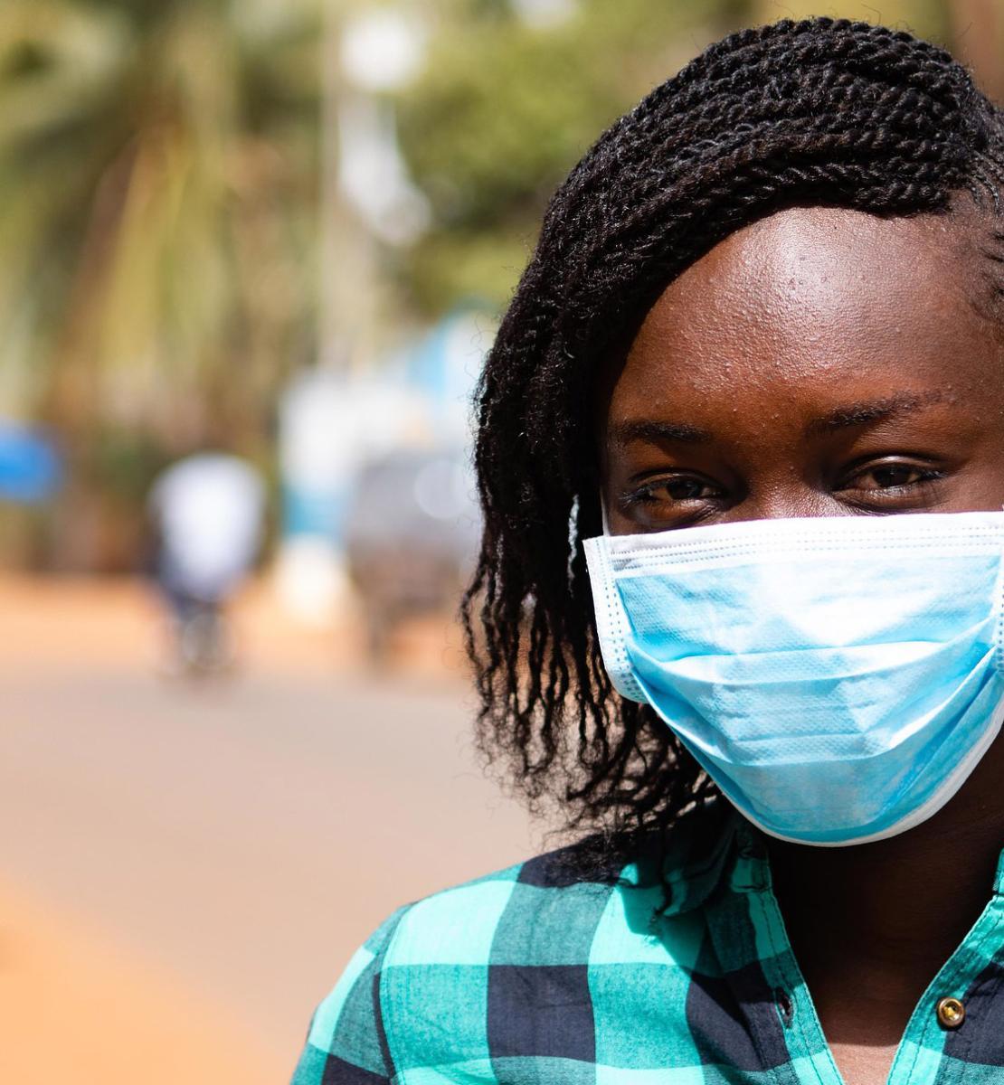 Un primer plano medio de una adolescente con una máscara facial mirando conmovedoramente a la cámara.