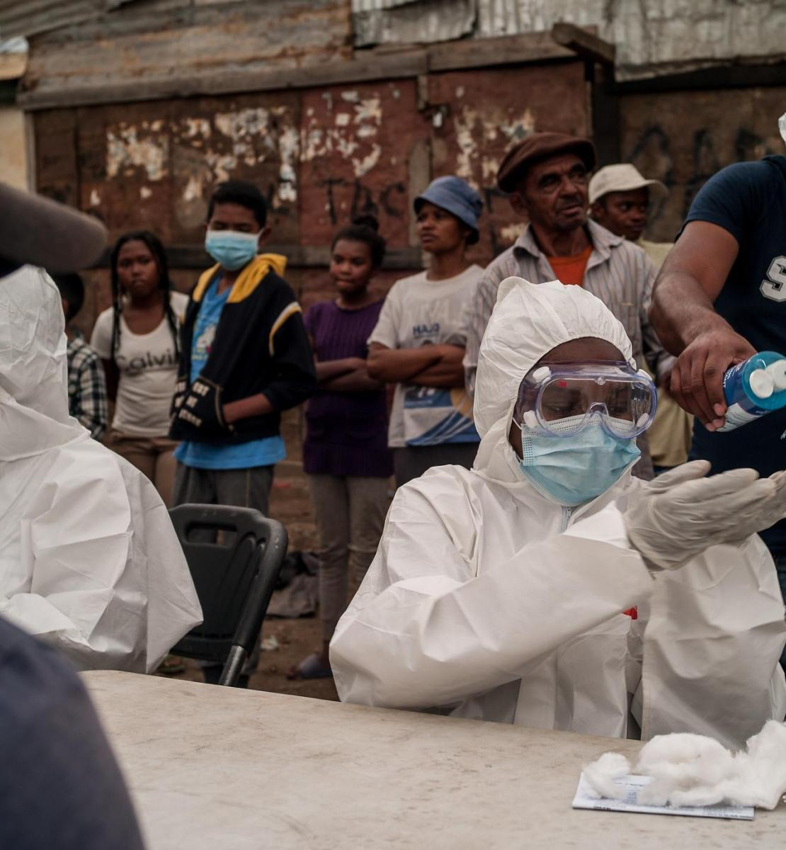 Image shows people waiting behind a table of healthcare workers wearing head-to-toe personal protective equipment. One man standing behind the healthcare workers pours had sanitizer onto the hands of one of the workers, while a man sits in front of her and waits.