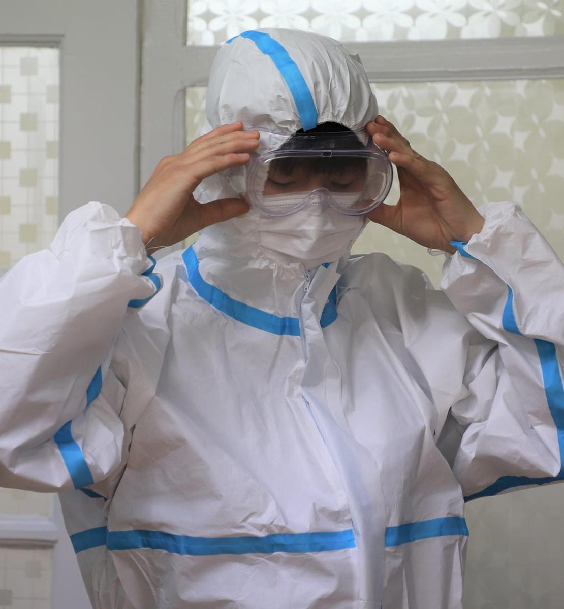 Медицинский работник примеряет костюм индивидуальной защиты.