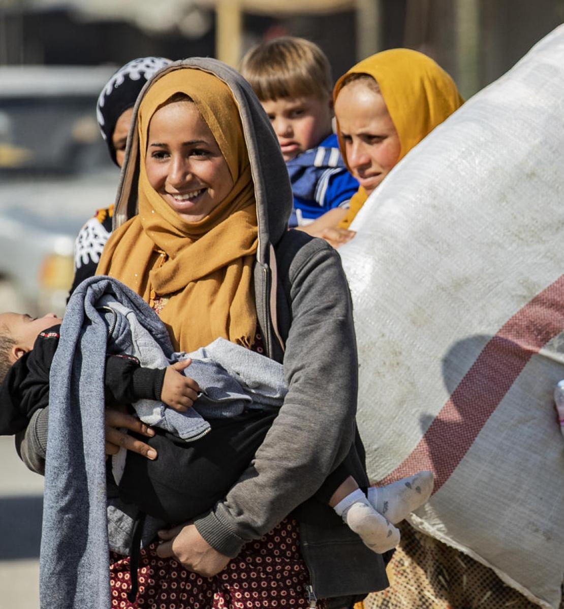 Una mujer sonríe mientras carga a un niño dormido. Otra mujer camina detrás de ella mientras lleva una bolsa grande.