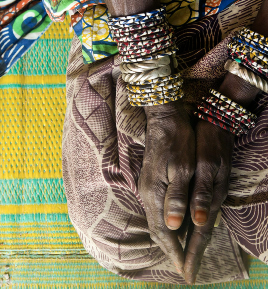 A woman's hands, with several bracelets, rest on her knees on top of a bright colored cloth.