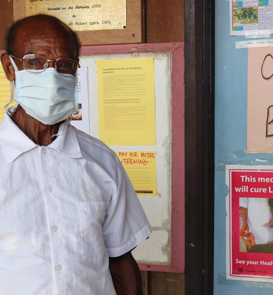 A man with a white shirt and a white face mask stands in front of a bulletin board with information on COVID-19.
