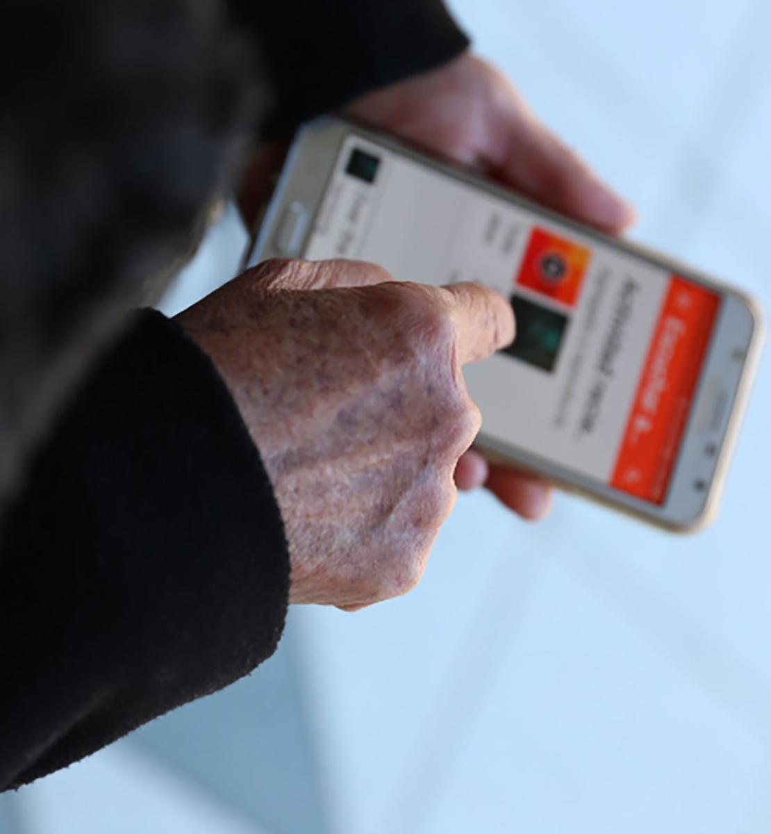 Imagen de las manos de una persona sujetando un teléfono móvil y utilizando una aplicación.