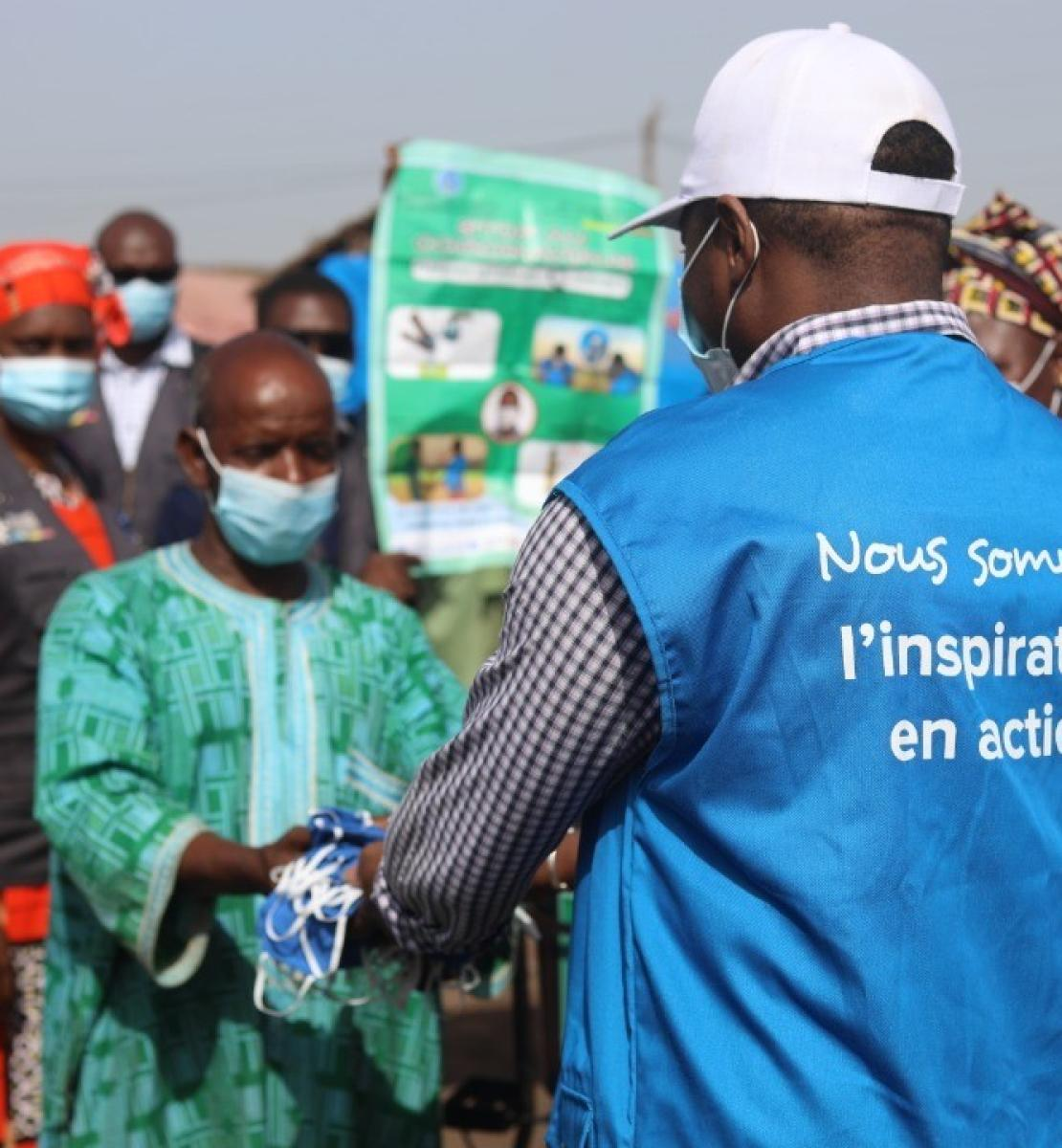 A United Nations Volunteer in a blue vest hands a man a bag. Several people stand behind the man receiving the package.