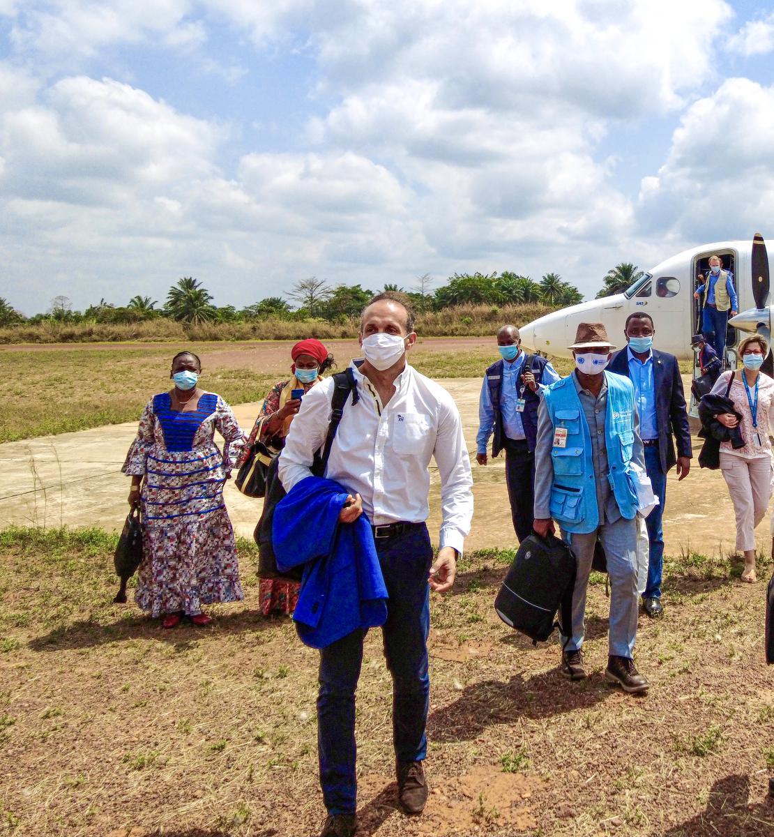 ينزل أشخاص عدة يرتدون أقنعة الوجه ويحملون أكياسًا وسترات إلى حقل في يوم مشمس.