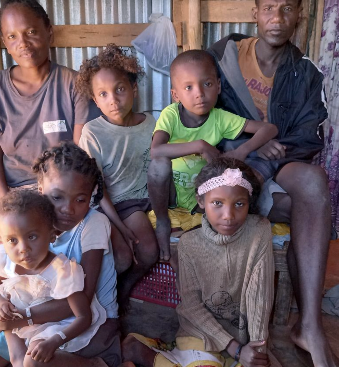 Fagnosea and Masy and their family sit together inside their home.