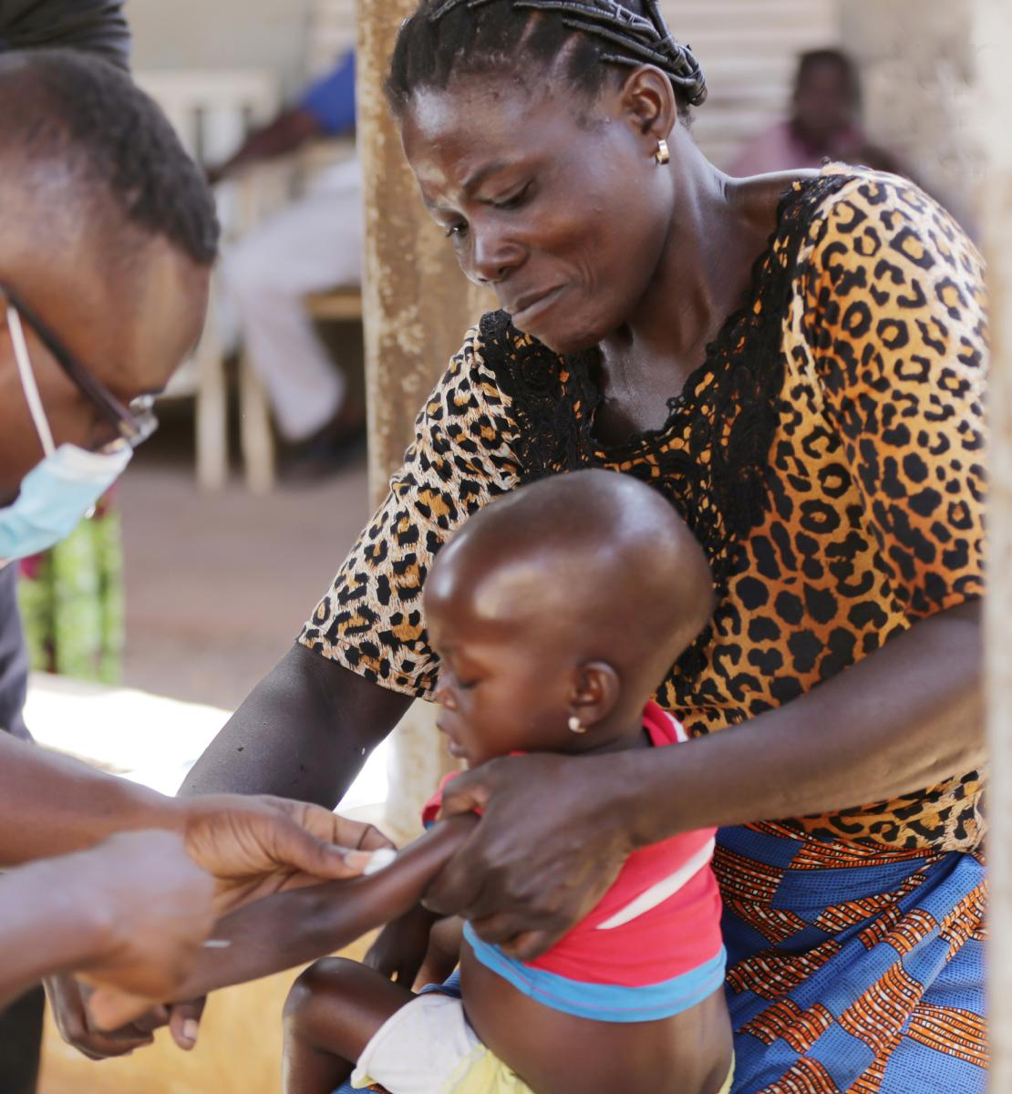 A child, held by a woman, receives an injection from a man in a yellow shirt.