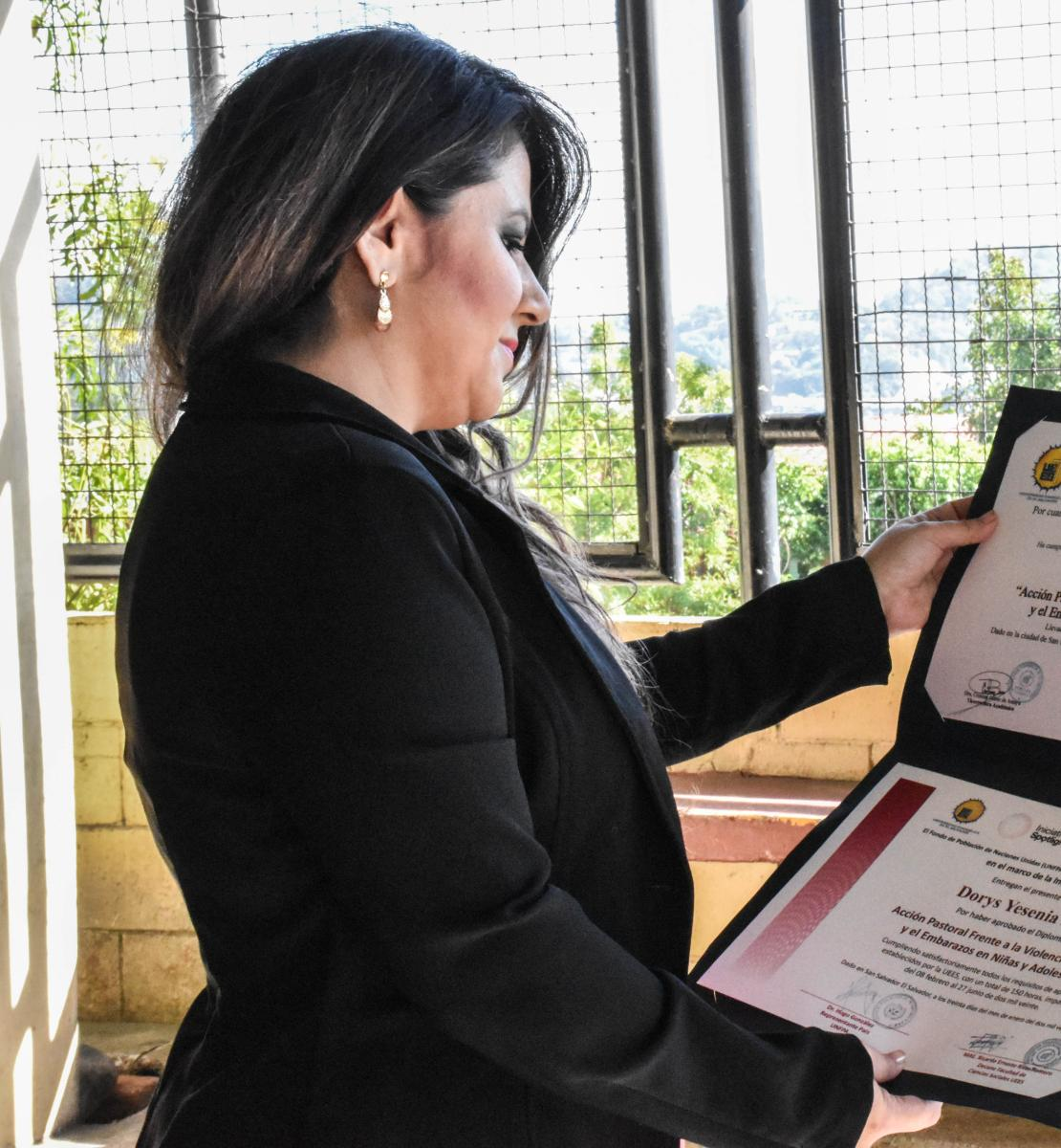 A woman with dark hair and a black jacket looks down at her diploma.