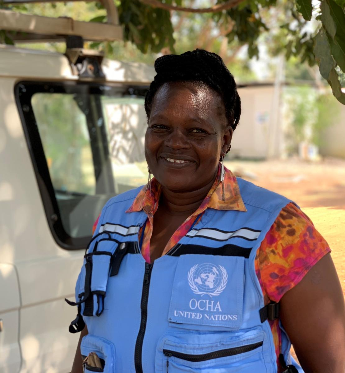 A woman in a light blue United Nations vest smiles at the camera.