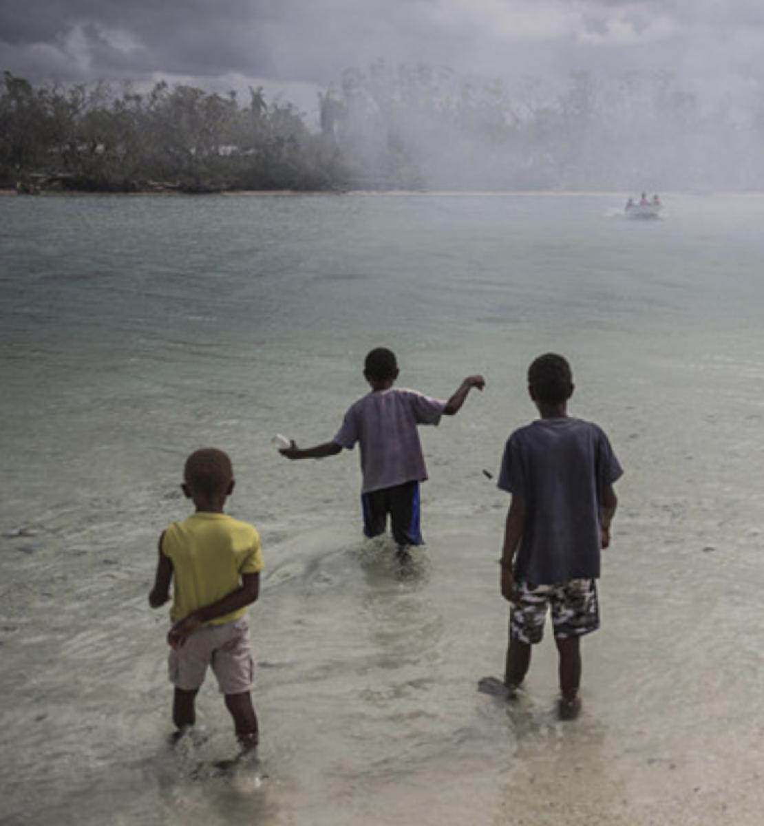 يقف ثلاثة أطفال في مسطح مائي وينظرون إلى قارب قريب.