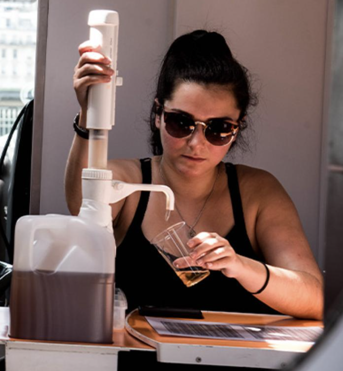 A woman is sitting at a table pouring a brownish-yellow liquid into a cup.