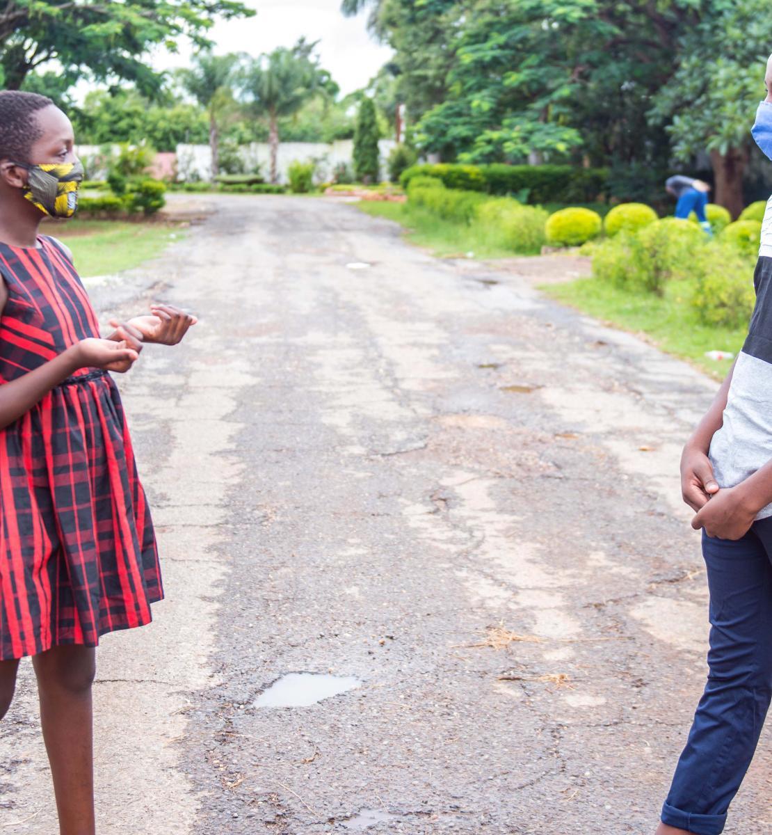 Une jeune adolescente et un jeune adolescent portant tous deux un masque de protection se tiennent debout au milieu d'une route à Lusaka, en Zambie. Il montrent comment se tenir à bonne distance l'un de l'autre pour se protéger contre une contamination à la COVID-19.