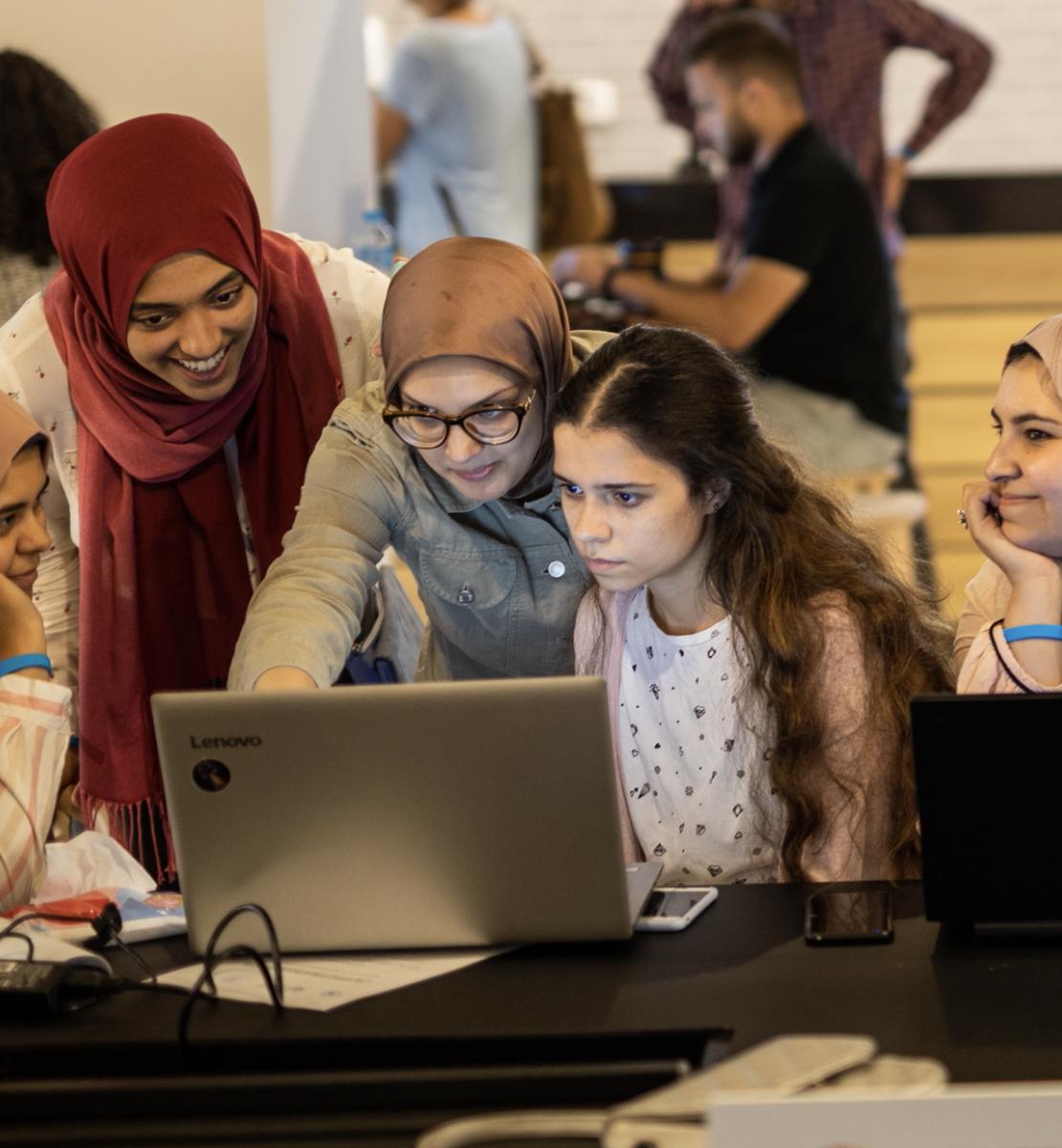 تنظر 5 فتيات إلى حاسوب محمول وسط مجموعة من الأشخاص.