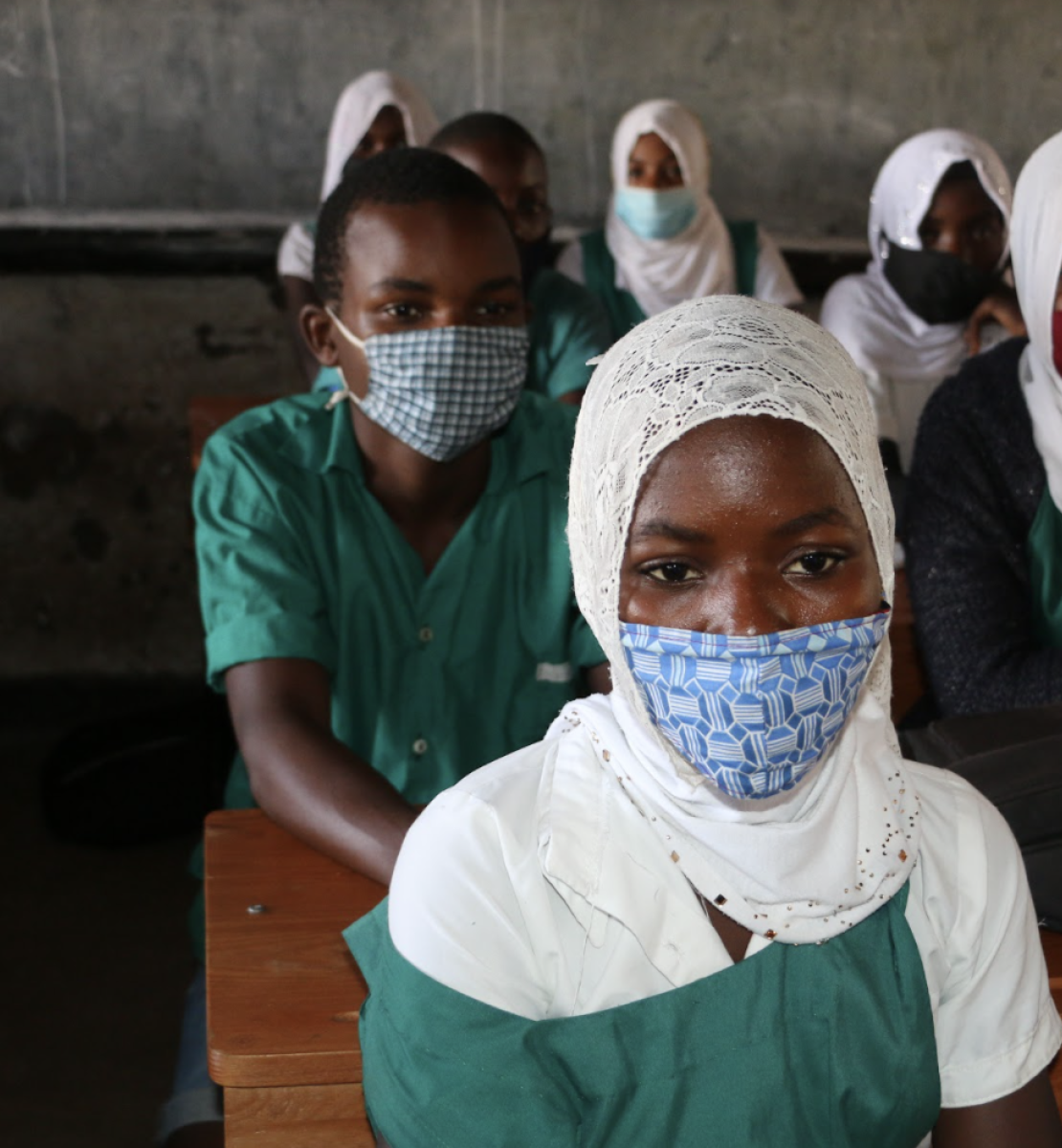 De jeunes élèves portant des uniformes scolaires et des masques de protection sont assis dans une salle de classe et regardent en direction du tableau.
