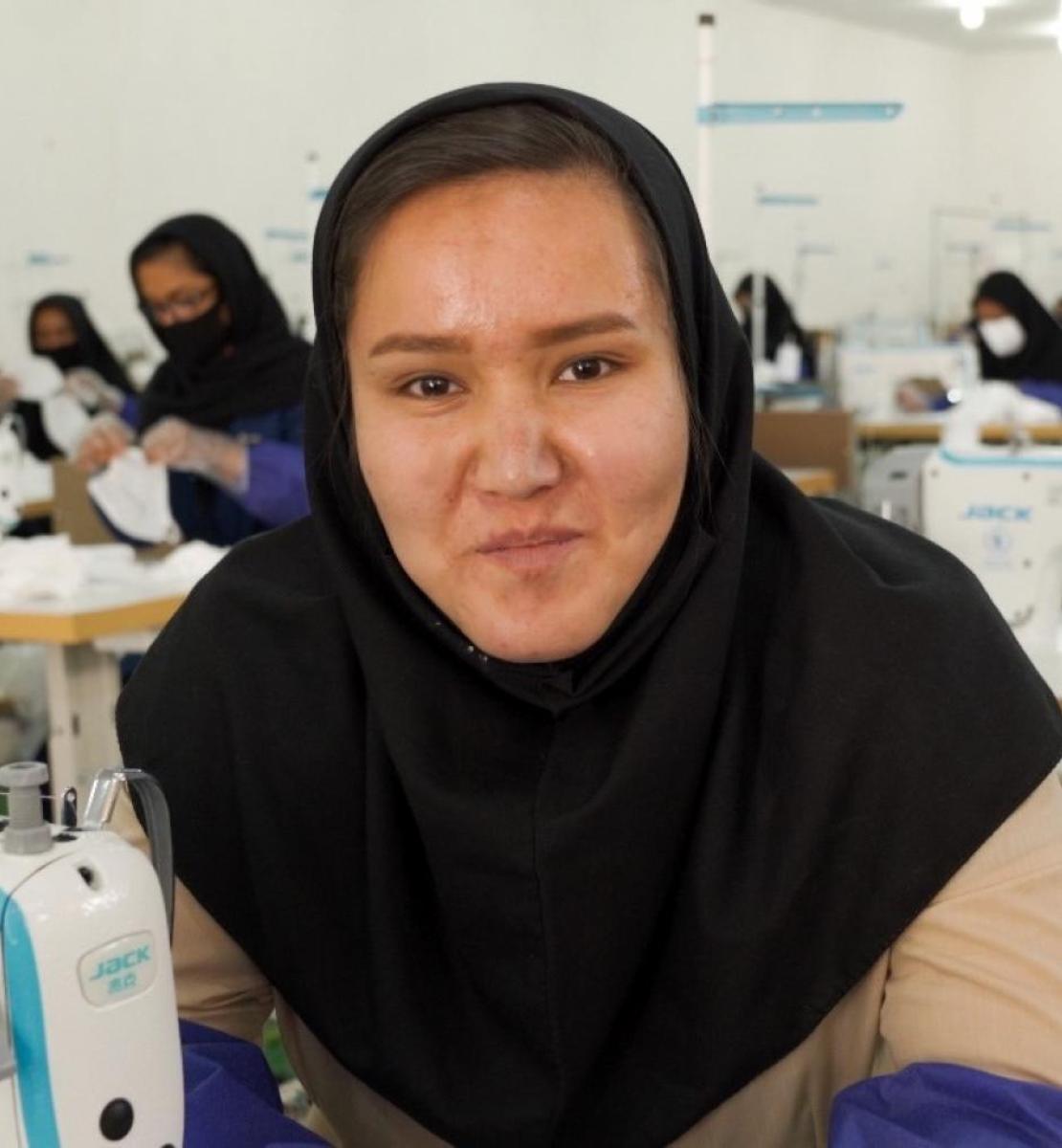 房间里满是在缝纫机前工作的妇女,其中一位年轻妇女直视着镜头。