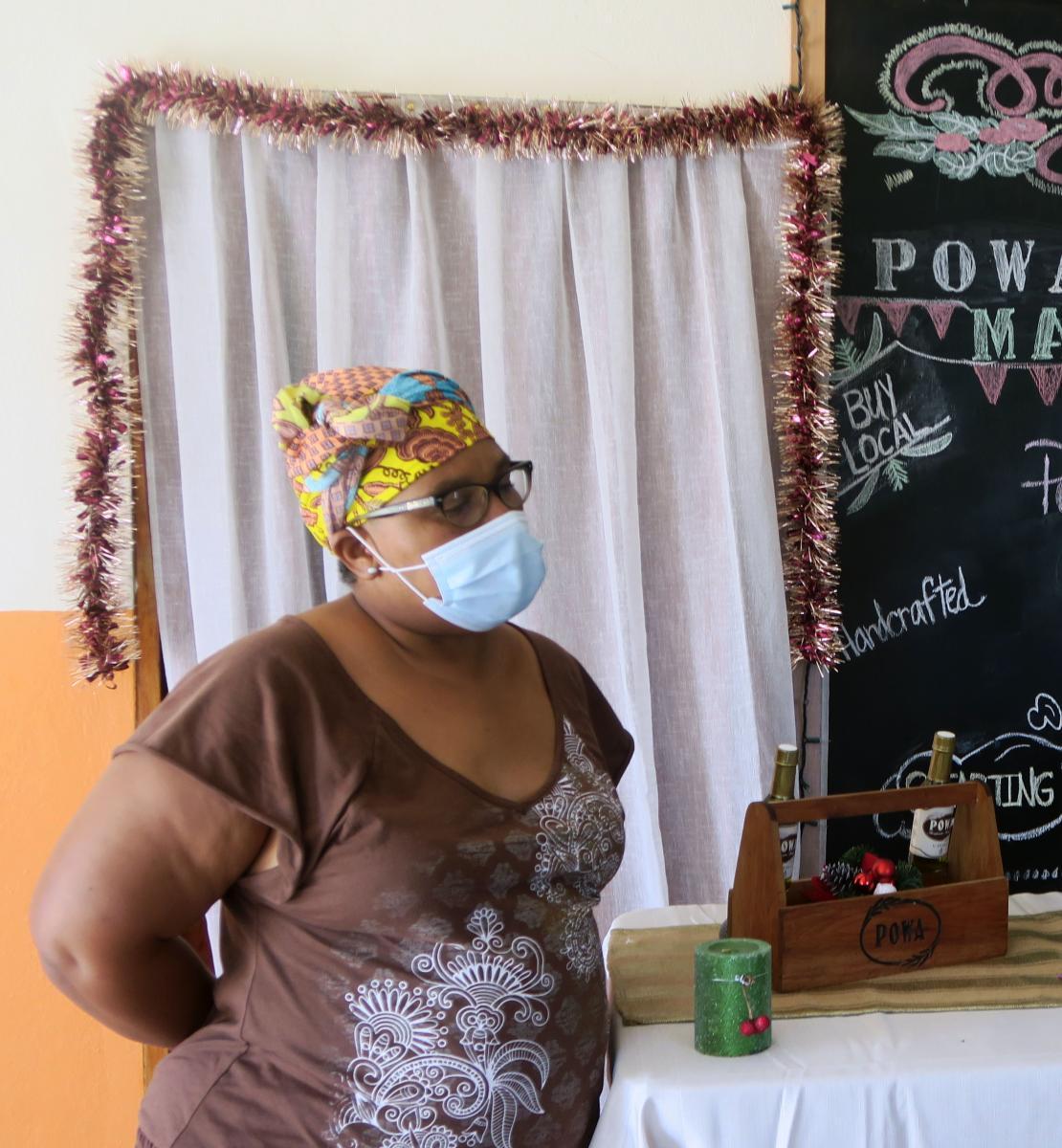 امرأة ترتدي كمامة تقف أمام زيوتها وصابونها محلي الصنع في سوق برعاية POWA.