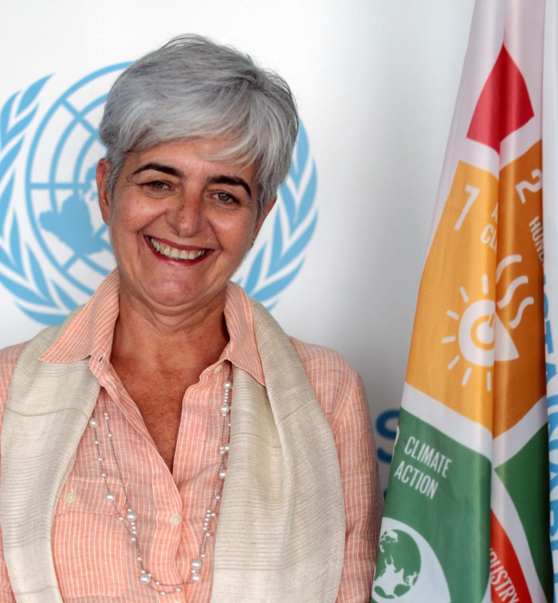 A woman smiles at the camera in front of the United Nations Sustainable Development Goals Flag and the United Nations Symbol.