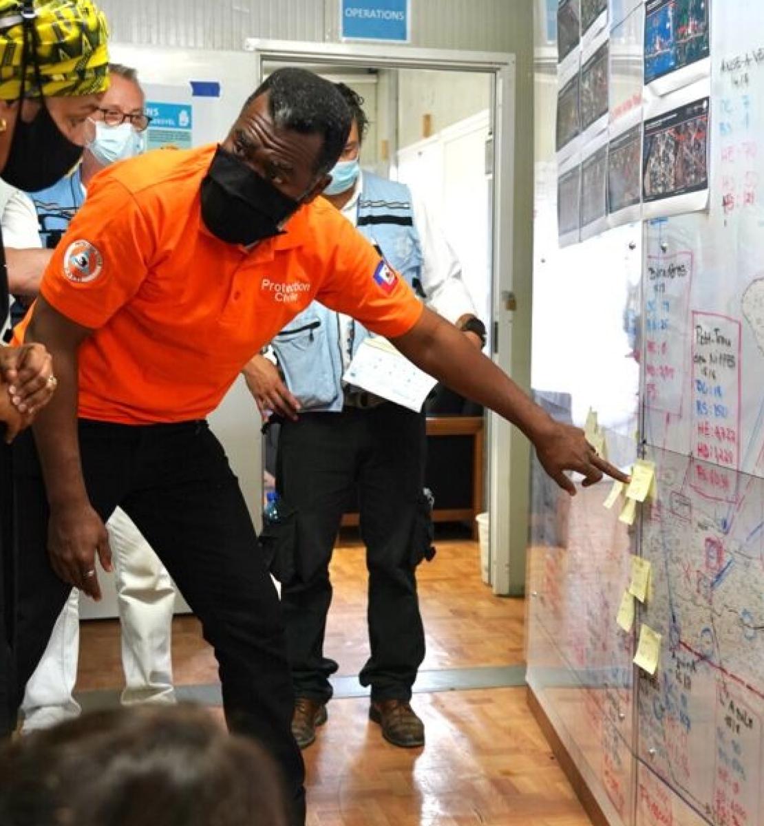 أحد أعضاء الفريق الإغاثي يشرح لنائبة الأمين العام أمينة محمد عن خطط الإغاثة.