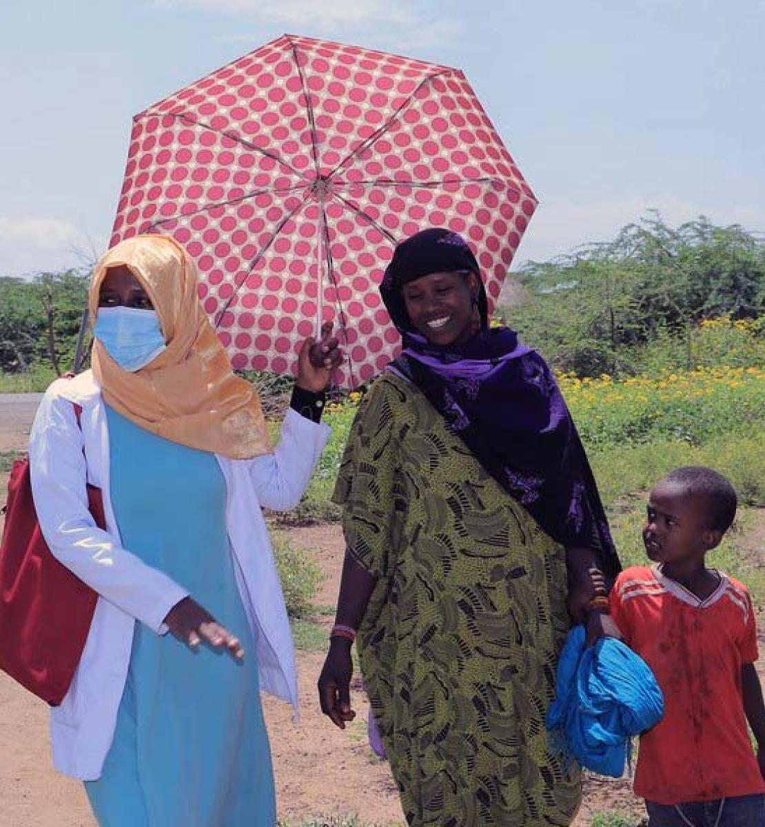 Une femme portant un masque de protection et tenant un parapluie marche sur un sentier de terre aux côtés d'une autre femme et de son jeune fils.