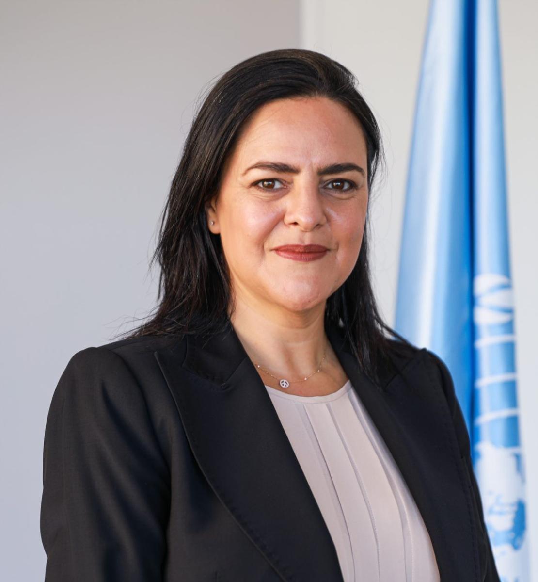 امرأة ترتدي سترة سوداء تنظر مباشرة إلى الكاميرا وخلفها علم الأمم المتحدة.