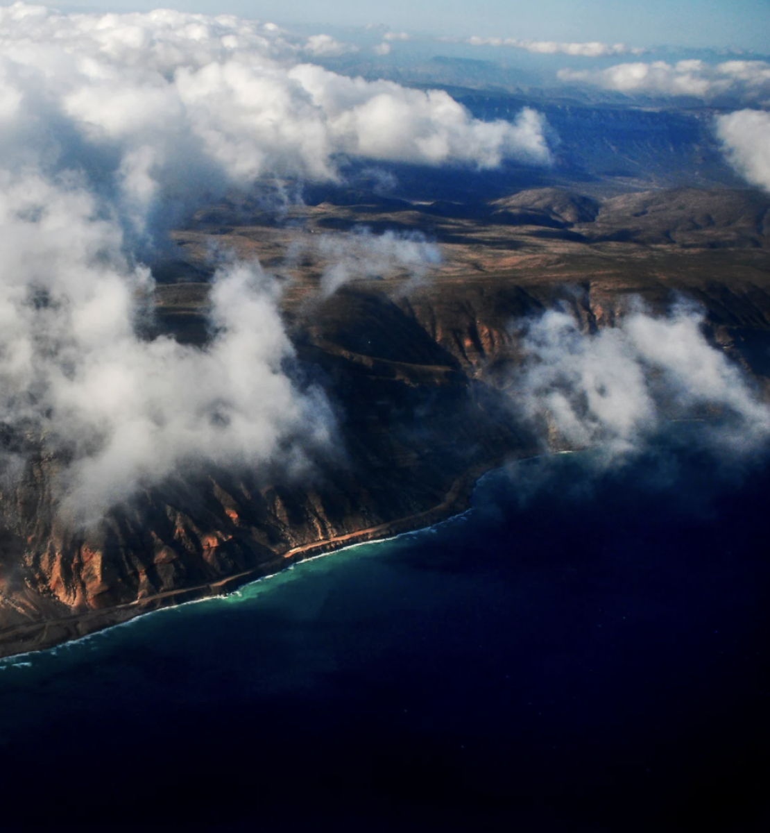 An areal shot of a coastline with clouds in the sky.