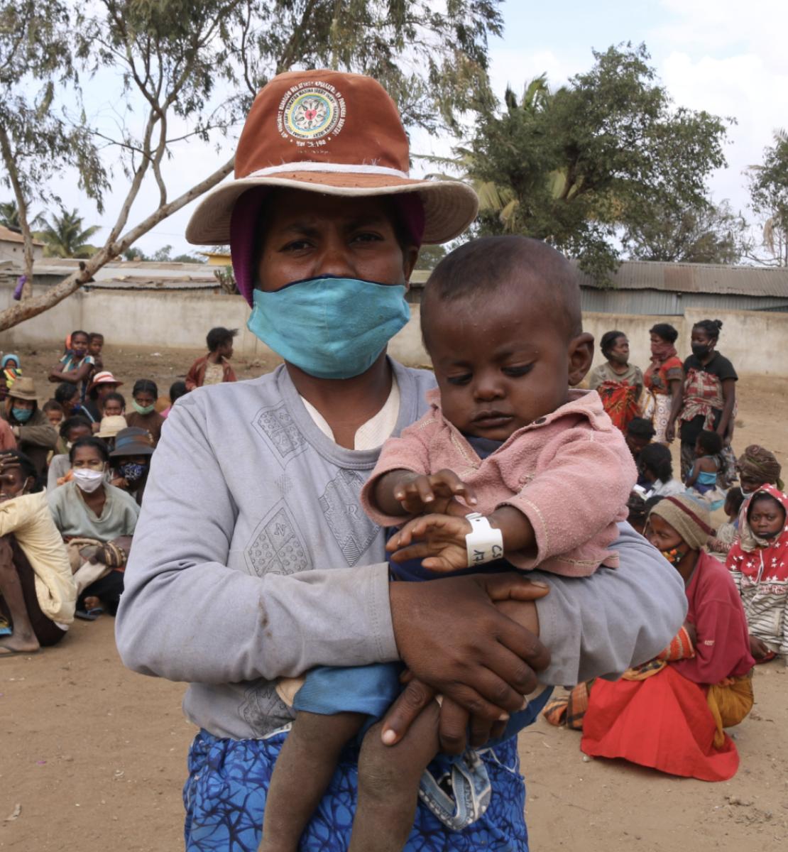 Une femme portant un masque de protection et un chapeau se tient debout dans une grande cour extérieure, face caméra, un bébé dans les bras, tandis que de nombreux enfants sont assis par terre, en arrière-plan.