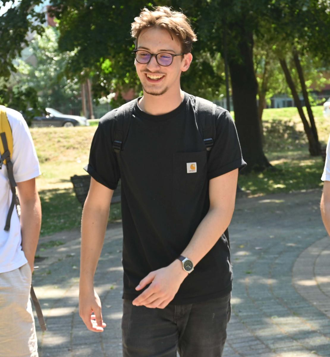 Three young men, Teo (left), Orhan (middle) and Boris (right), walk happily together in a park.