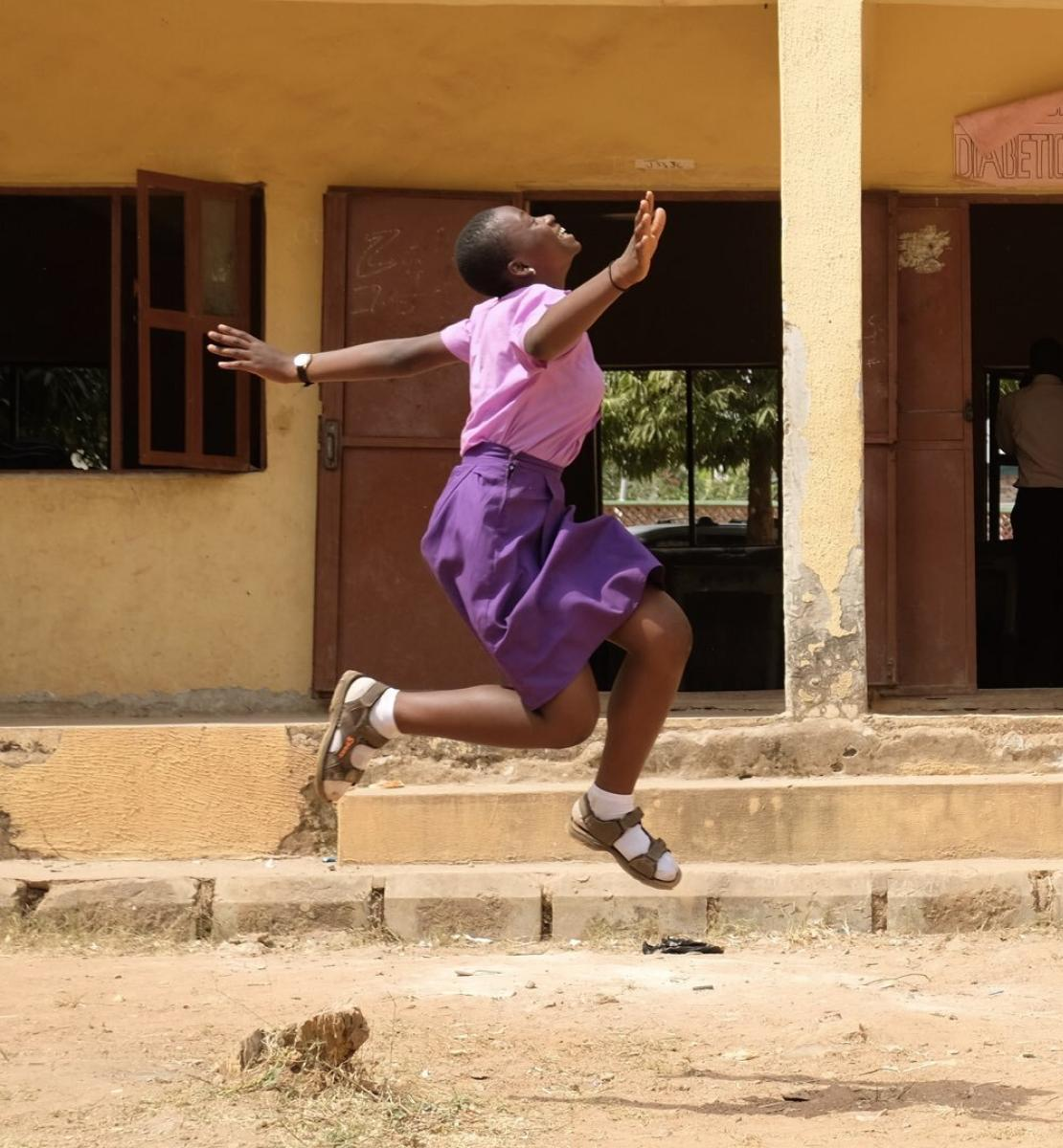 A young girl in a pink shirt and purple dress jumps near a school building.