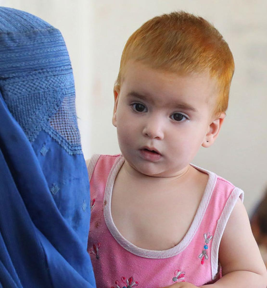 A mother in the forefront is shown wearing a headdress and face as she holds her baby and in the background is another mother and child.
