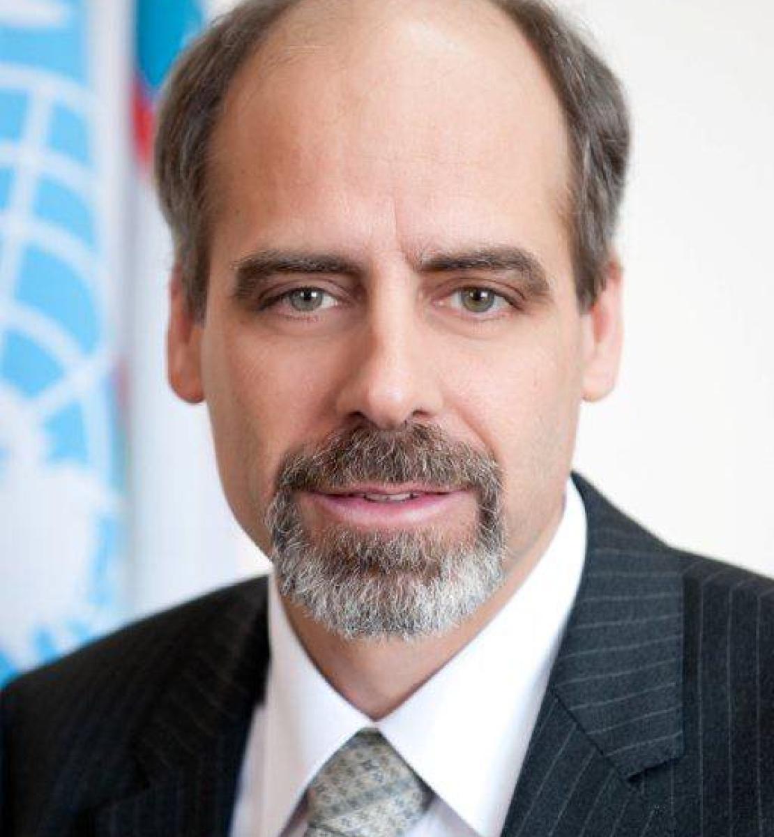 一个男人直视镜头,背景是联合国的旗帜。