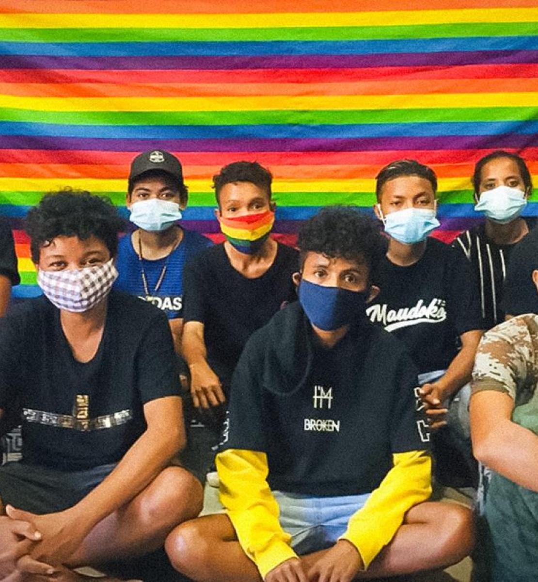 一群戴着口罩的年轻人在一面彩虹色的旗帜前盘腿而坐。