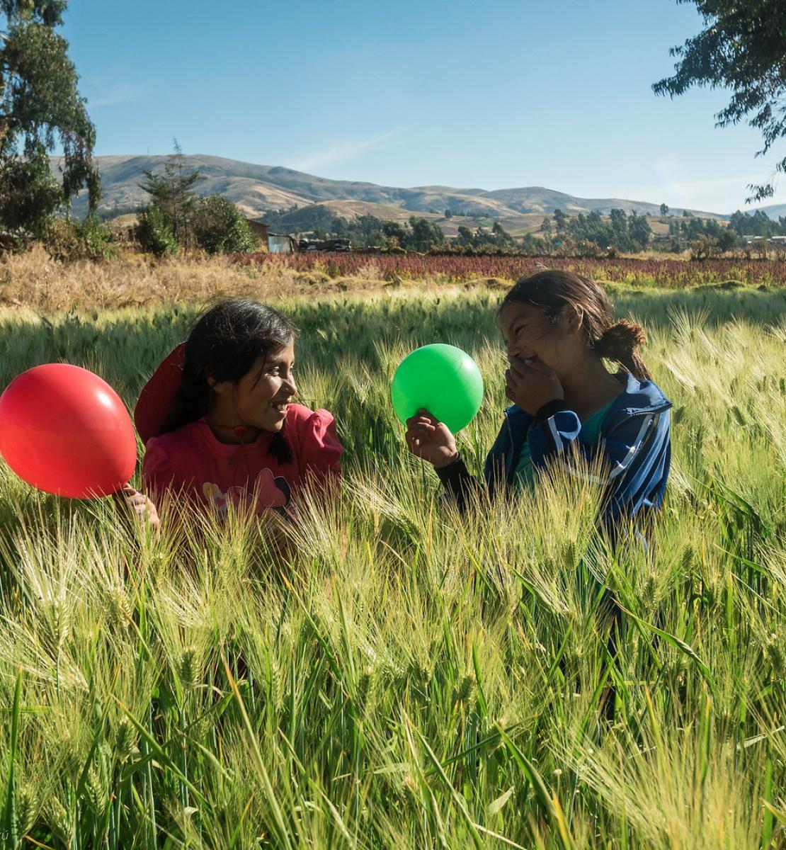 فتاتان في حقل تلعبان ببالونين أخضر وأحمر.