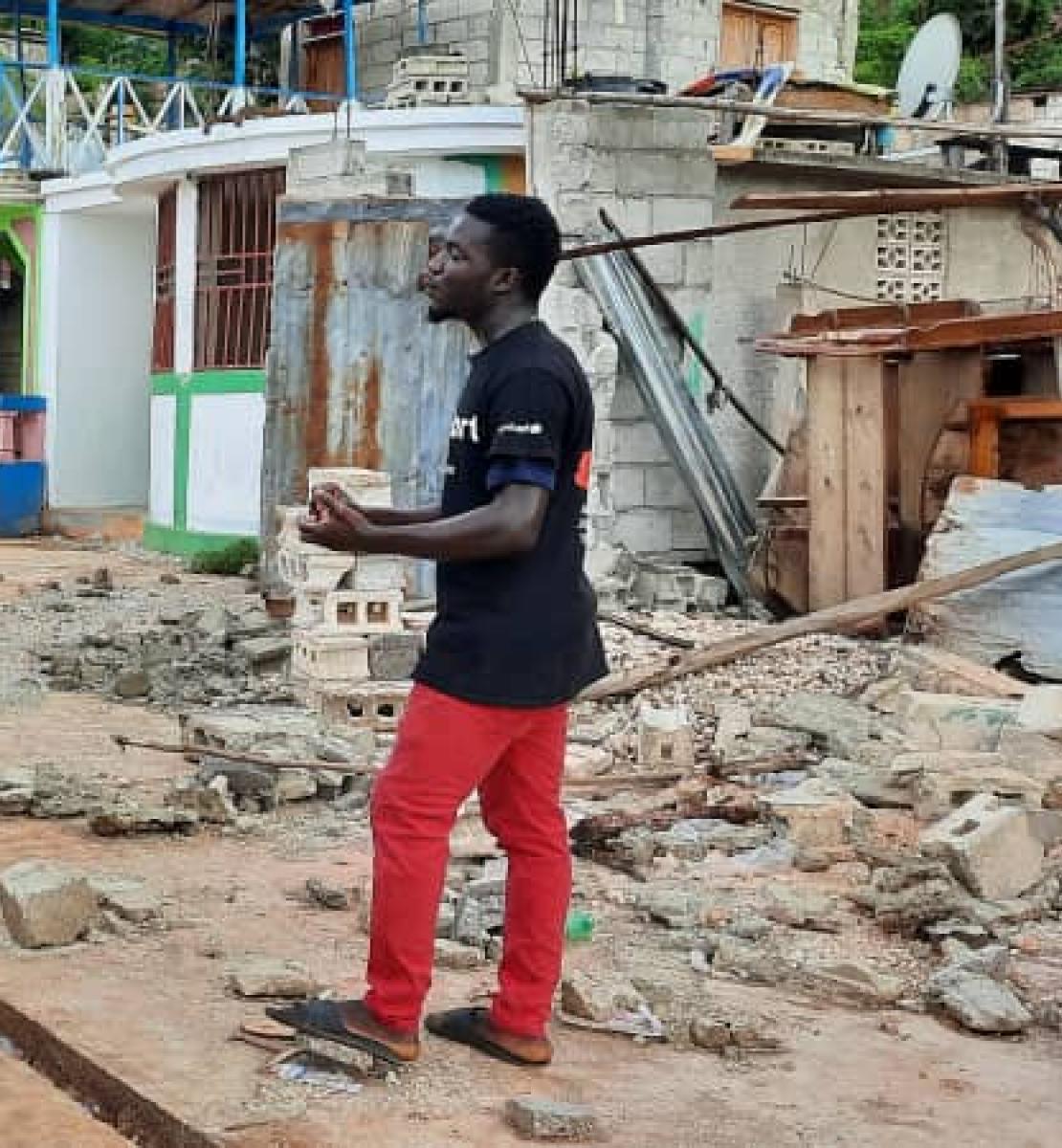 شاب يرتدي سروالًا أحمر يتحدث إلى مجموعة كبيرة من المتطوعين وعمال الإغاثة بالقرب من أنقاض الزلزال.