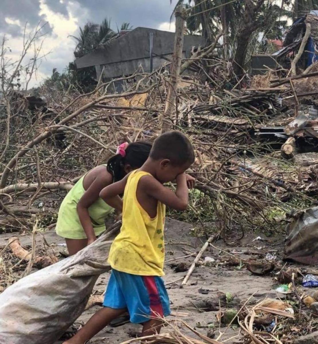 طفلان يمشيان ويجرّان كيسًا بالقرب من حطام منزل.