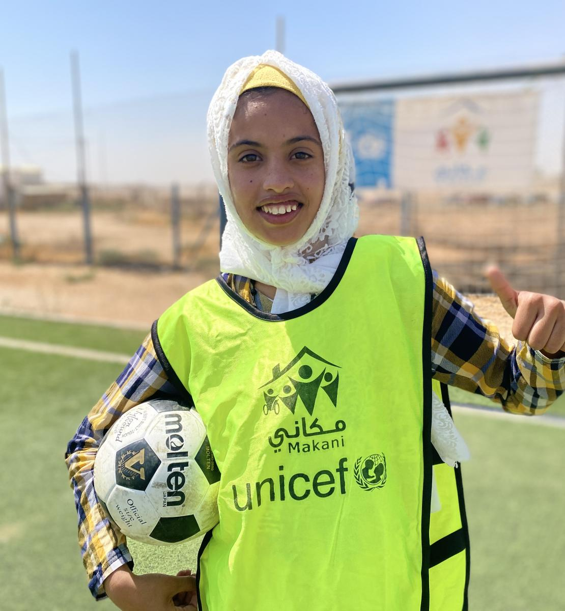 Sur un terrain de football, une jeune fille tient un ballon de football sous le bras et lève le pouce de l'autre main en souriant à l'objectif. Elle porte un foulard blanc sur la tête et est vêtue d'un maillot de couleur jaune portant le logo de l'UNICEF et celui du programme Makani.