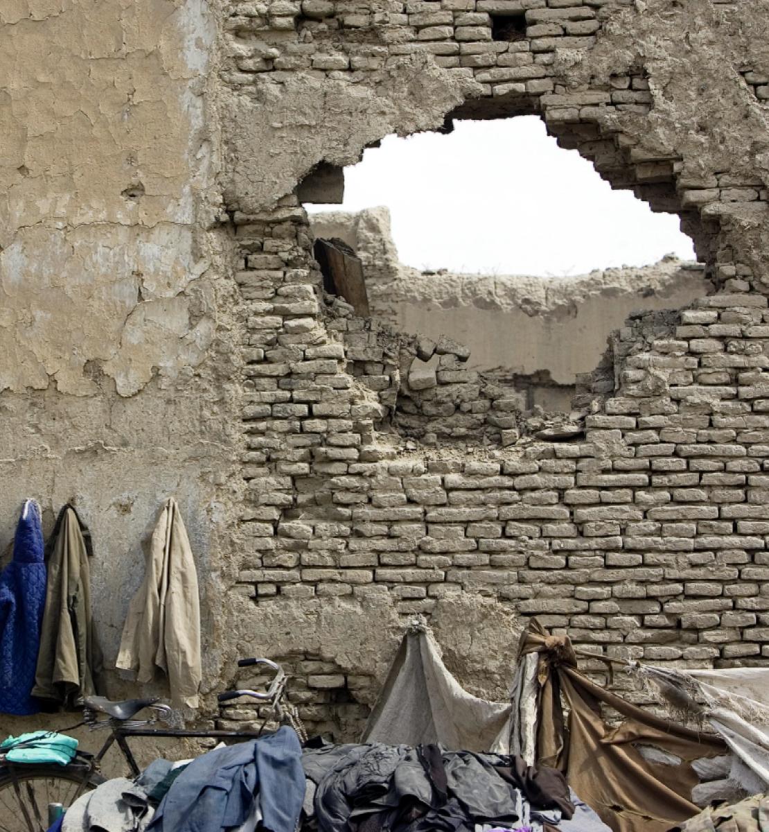 Plusieurs vestes sont suspendues sur le mur extérieur d'une façade en pierre dont une partie a été éventrée, laissant apparaître un trou béant.