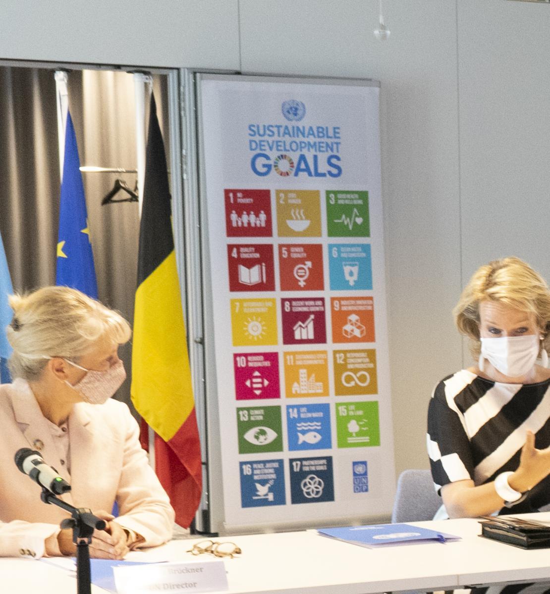 La Directrice du bureau de l'ONU/du PNUD à Bruxelles et Sa Majesté la Reine de Belges sont assises côte à côte à une table sur laquelle sont posés des microphones. Elles portent toutes deux un masque de protection respiratoire. En arrière-plan est installé un tableau sur lequel sont affichés les logos des ODD.
