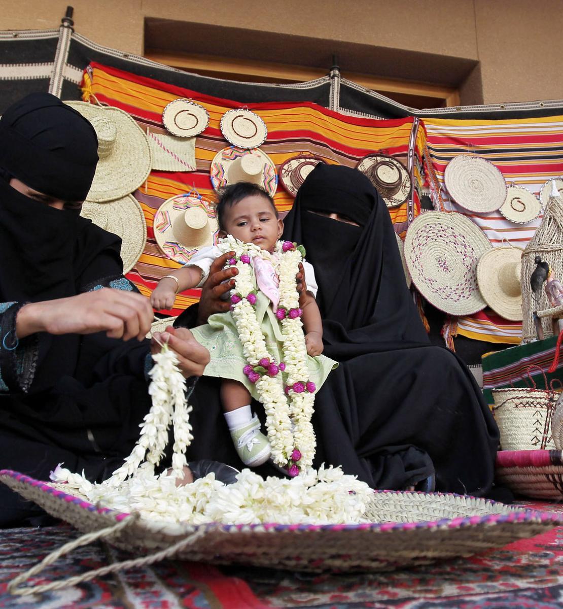 Deux femmes saoudiennes portant un voile intégrale noir sont assises sur un tapis, à même le sol, dans un souk. L'une d'elles fabrique des colliers de fleurs fraîches, tandis que l'autre, assise juste à côté, la regarde faire en tenant un bébé dans les bras. On aperçoit en arrière-plan des objets de fabrication artisanale accrochés à une étoffe en couleurs.
