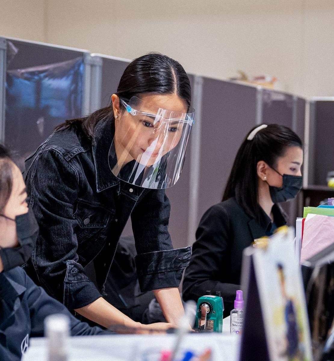 تعمل النساء اللائي يرتدين أقنعة واقية ودروعًا للوجه في أحد المكاتب.