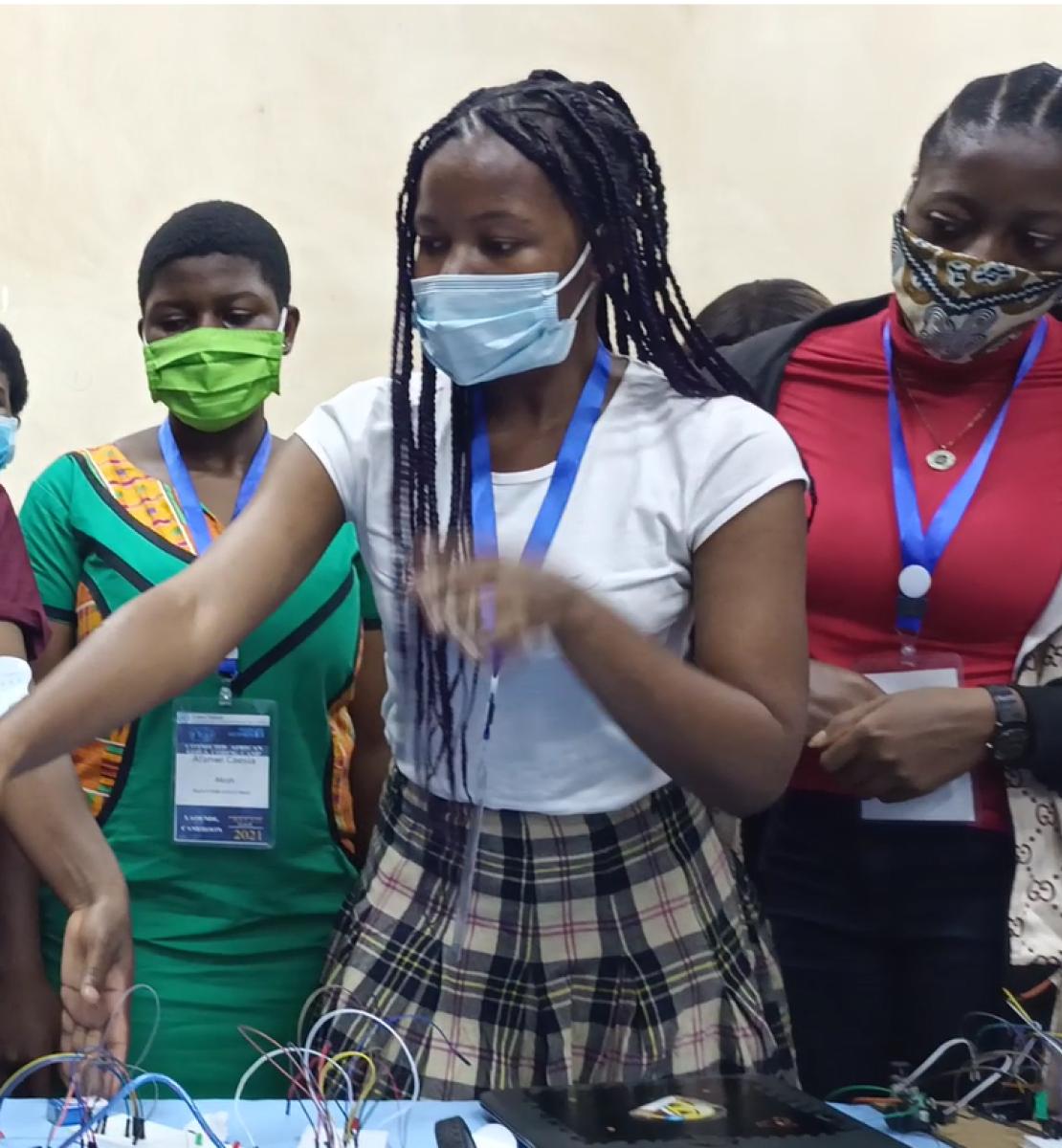 Un grupo de chicas jóvenes con mascarillas señalan hacia el contenido de una pantalla.