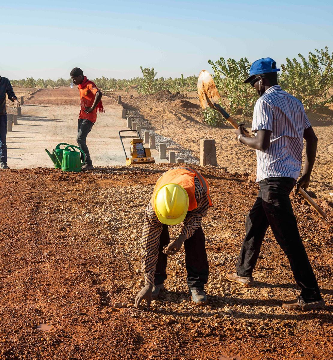 Quatre hommes travaillent à la construction d'une piste au milieu d'un terrain désertique parsemé d'arbustes.