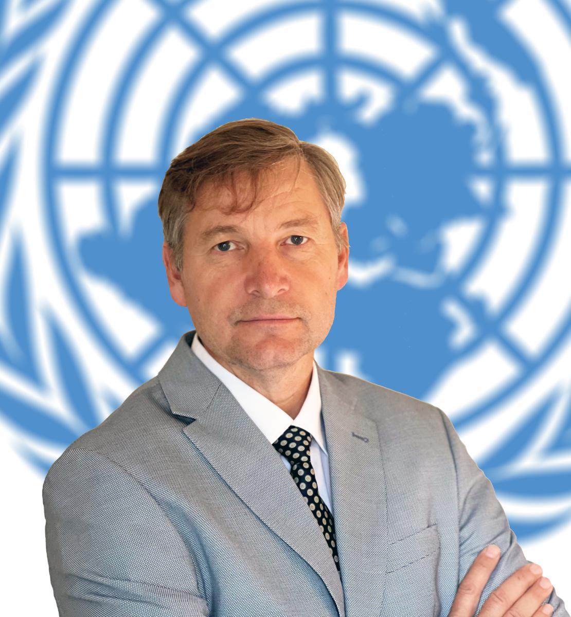 Un homme en costume gris se tient devant l'emblème des Nations Unies et regarde l'objectif, les bras croisés.
