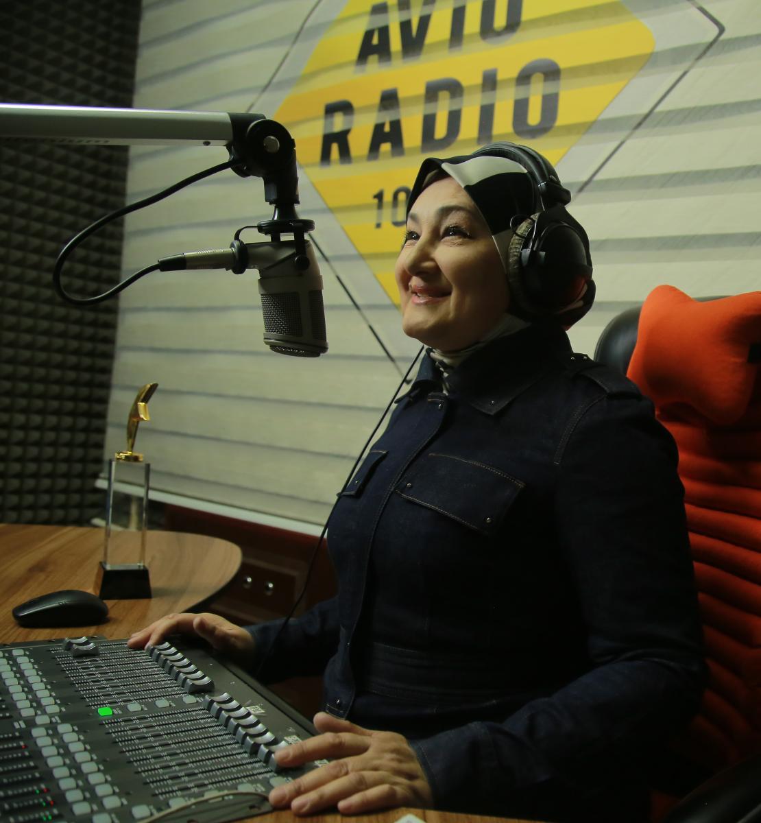 امرأة ترتدي ملابس سوداء تجلس على مكتب وأمامها ميكروفون ومعدات إذاعية.