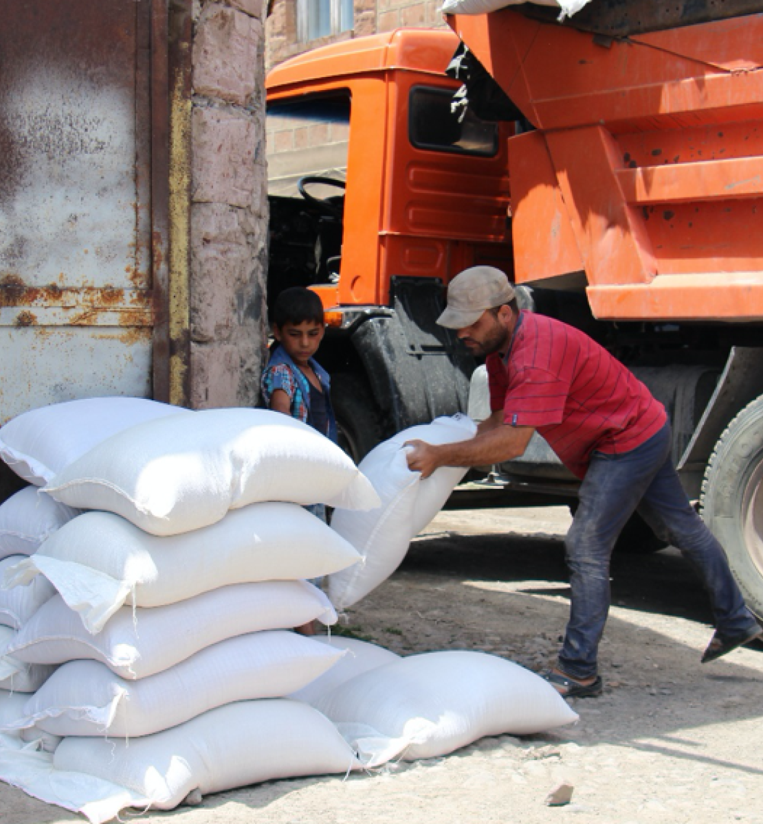 A man in a red shirt unloads white bags from a large orange truck while a small child looks on.
