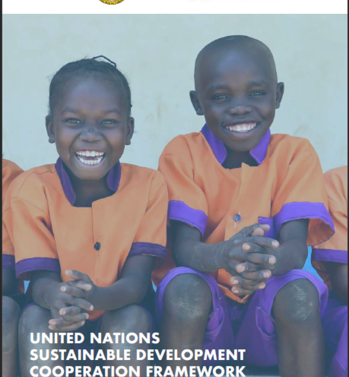 The cover shows two smiling children in school uniforms sit and face the camera with the title at the bottom of the page with the government and UNCT logos at the top.